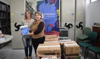 Coordenadora da Biblioteca Central, Eliane Dittrich (E), recebe os livros da chefe do Departamento de Administração Pública da Udesc Esag, Ivoneti Ramos - Foto: Luiza Pereira/Ascom/Udesc Esag