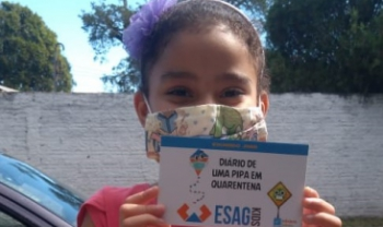 Menina recebe doação de um dos livros do Esag Kids