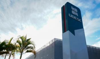 Na imagem, aparece um totem verde e branco com a marca da Udesc em primeiro plano; atrás, há o prédio da Reitoria, algumas palmeiras e um céu parcialmente nublado.